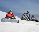 Four snowboarders sitting on ski slope, smiling, portrait
