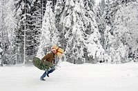 Man running in snow, carrying christmas tree and present