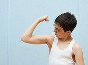 Boy (11-13) flexing muscles