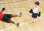 Boy (5-7) with boxing gloves standing beside unconscious man in gym