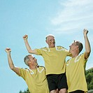 Three mature football players celebrating, low angle view