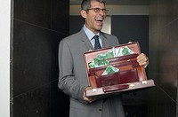 Businessman holding open briefcase full of euro banknotes, laughing