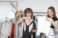 Two teenage girls (16-18) looking at clothing, smiling