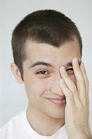 Portrait of young man, covering face with hand
