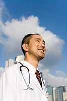 Doctor standing outdoors, smiling, low angle view