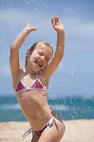 Girl (5-7) playing in water spray on beach, arms raised, eyes closed