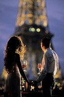 Couple with champagne glasses on River Seine houseboat under Eiffel Tower