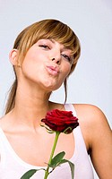 Young woman holding red rose, pouting, portrait, close-up