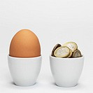 Egg and Euro coins in egg cups, close-up