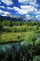 Woman fishing along Snake River below Grand Tetons Wyoming USA