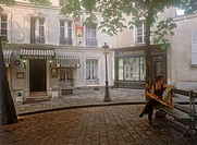 Parisian woman with baguette resting in small quiet Montmartre square