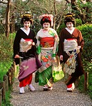Geisha women in colorful dress on pathway in Tokyo park