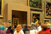 Visitors looking at painting of Mona Lisa by Leonardo da Vinci in the Louvre Museum