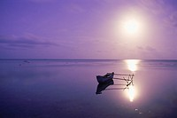 Outrigger in calm lagoon off Aitutaki Island under full moon in South Pacific