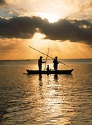 Family in outrigger canoe spearfishing on Aitutaki lagoon at sunset