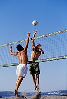 Two men in swimsuits leap upwards, one to spike and the other to block a volleyball across the net during a game on the beach
