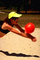 Female volleyball player lunging at ball while playing at the beach