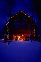 Cabin in the snow with Christmas lights and evening light  Property released