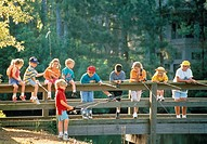 Group of children standing in a line and looking over the railing of a bridge while a few of them are fishing off the bridge
