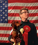 Beribboned man and his prize-winning dachshund standing in front of U S  flag at dog show