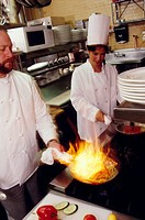 Two chefs cooking on a stove in a restaurant kitchen  One of their pans is deliberately aflame