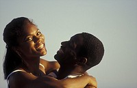 Close-up of a happy African-American couple embracing outdoors