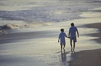 Father and son walk hand-in-hand barefoot in the wet sand of a beach