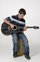 Teenage boy (16-17) playing guitar in studio