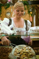 Young woman in Bavarian national dress, working behind shop counter