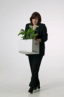 Woman carrying plant in carton, in studio