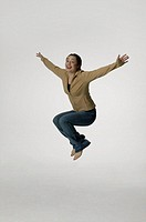 Young woman jumping with arms out in studio, portrait