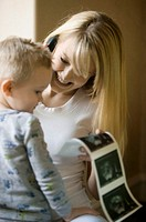 Pregnant woman showing ultrasound pictures to son (3-4) in room