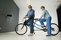 Senior couple sitting on  tandem bicycle, posing in studio, portrait