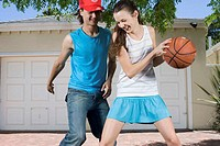 Two Teenagers Playing Basketball in Driveway (thumbnail)