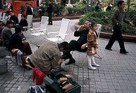 Morning shoe shine in city park, father on cell phone, daughter near, business, Wuxi, China, Asia, 042503