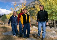 A family of four hiking amid fall color in Rocky Mtns of CO.