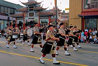 Band of scottish bagpipe players marching along Broadway through the Los Angeles Chinatown during Chinese New Years celebrations