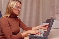 Blonde woman wearing a brown turtleneck and glasses working on her laptop in an office.