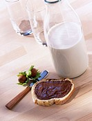 Hazelnut spread on slice of bread with knife and bottle of milk