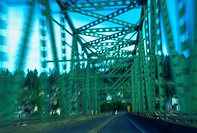 View from inside a speeding car while driving on a suspension bridge.