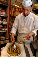 Chef putting olives from a bowl into a plastic bag, Venice, Veneto, Italy