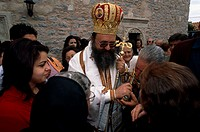 Senior woman kissing a cross held by a priest, Crete, Greece