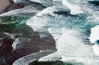 Hawaii, Big Island, Waipio Valley, Black sand beach, surfer walking out into pattern of rolling waves.