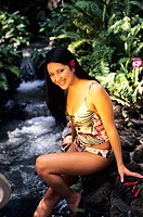 Beautiful Hawaiian girl in swimsuit sitting on rocks by creek in rainforest.