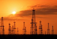 Oil derricks silhouetted against sunset skies