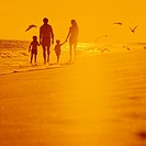 Father, mother and two children holding hands as they walk along the ocean shore as the sun rises.