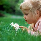 Close-up of a young girl with long blond hair laying in the grass looking closely at a flower that is growing in the grass.