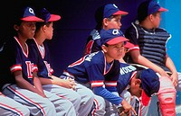 Young baseball players watch action from the bench, Caracas, Venezuela.