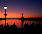 Silhouettes of people sitting beside Chania harbor with Venetian Lighthouse in background in late dusk, western Crete, Greece.