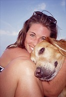Portrait of young adult lady embracing her yellow Labrador retriever.